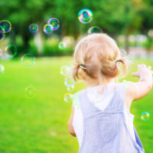 Toddler chasing bubbles