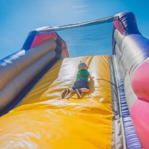 Child sliding down a bouncy castle