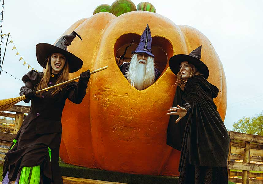 Witches and wizard with a giant pumpkin